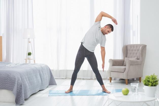 Fuerte y sano. buen hombre agradable haciendo un ejercicio mientras disfruta del deporte