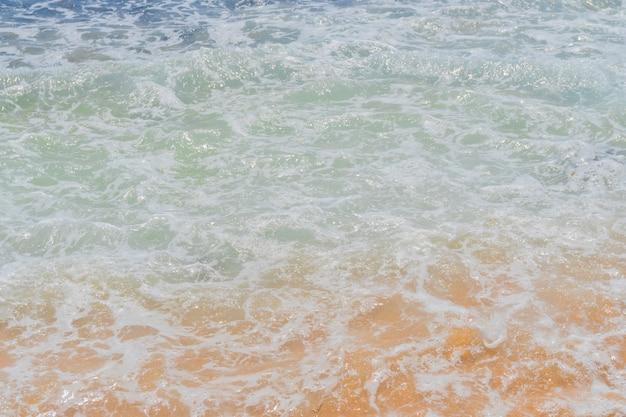 Fuertes olas costeras en la orilla arenosa del océano.