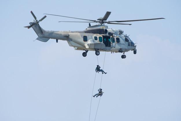 Fuerzas especiales muestran con soldado o piloto saltar desde helicóptero con cielo azul