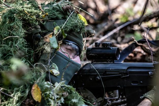 Fuerzas especiales, rifle de asalto soldado con silenciador, mira óptica. detrás de la cubierta esperando en una emboscada