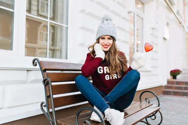 Full-lenth hermosa joven con pelo largo en sombrero de punto y guantes blancos sentado en un banco en la ciudad. ella tiene corazón de caramelo, sonriendo.