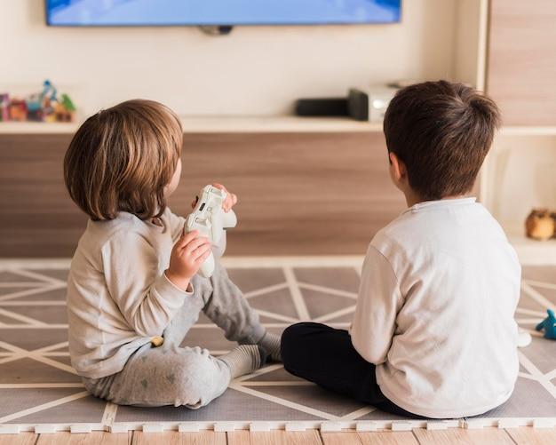 Full shot niños jugando con controlador