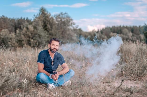 Fumador barbudo con estilo explota un par de un dispositivo de humo electrónico en la tranquilidad del aire libre