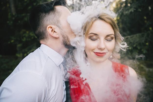 Fumador vape masculino soplando una espesa nube de humo al oído de su novia alegre y sonriente en vestido rojo con cara divertida y emocional.