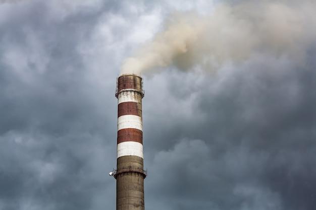 Fumar chimenea industrial en nubes oscuras. concepto para la protección del medio ambiente.