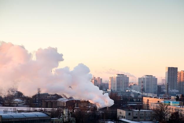 Fumar las chimeneas industriales al amanecer. concepto para la protección del medio ambiente