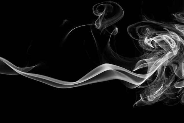Fume el incienso blanco sobre un fondo negro. concepto de oscuridad