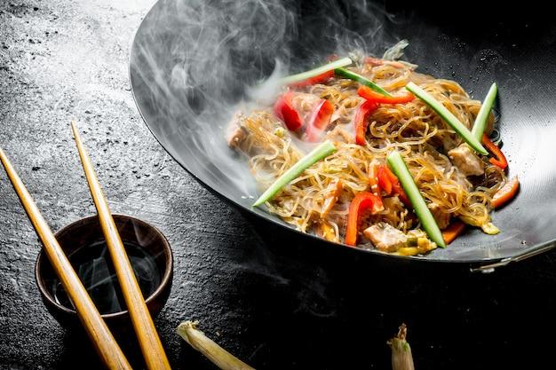 Funchoza china caliente con pollo y verduras en mesa rústica negra