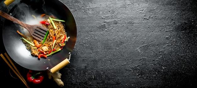 Funchoza china fragante con verduras frescas. en mesa rústica