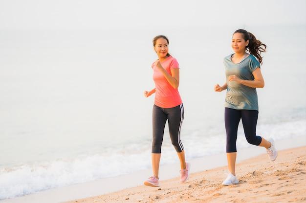 Funcionamiento y ejercicio asiáticos de la mujer del deporte joven hermoso del retrato en la playa cerca del mar y del océano en el tiempo de la salida del sol o de la puesta del sol