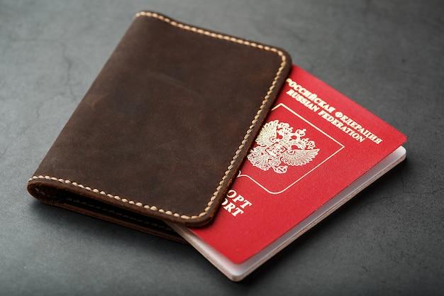 Funda de cuero marrón con pasaporte rojo.