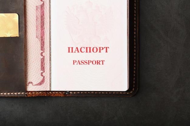 Funda de cuero para pasaporte abierta con tarjeta de crédito dorada