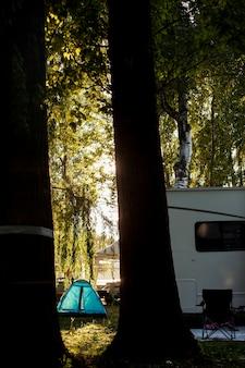 Furgoneta blanca y carpa azul en el bosque para acampar