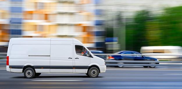 La furgoneta blanca conduce sobre el tráfico de la ciudad en el fondo del paisaje urbano.