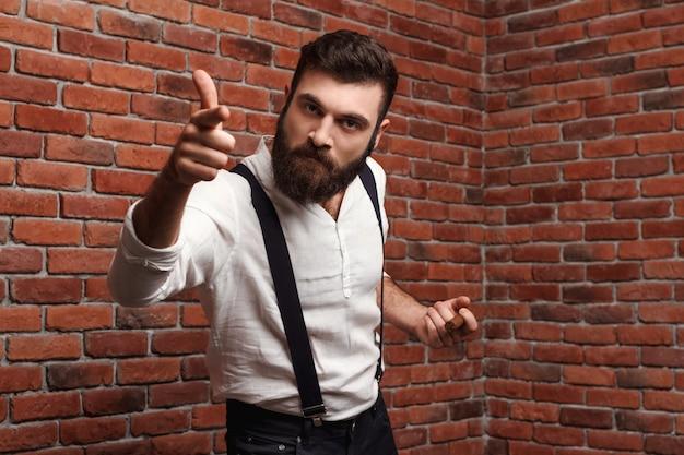Furia brutal joven guapo fumar cigarro en la pared de ladrillo.