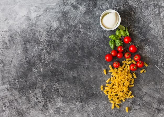 Fusilli crudo con tomates cherry; hojas de albahaca; pimienta negra y queso sobre fondo de textura