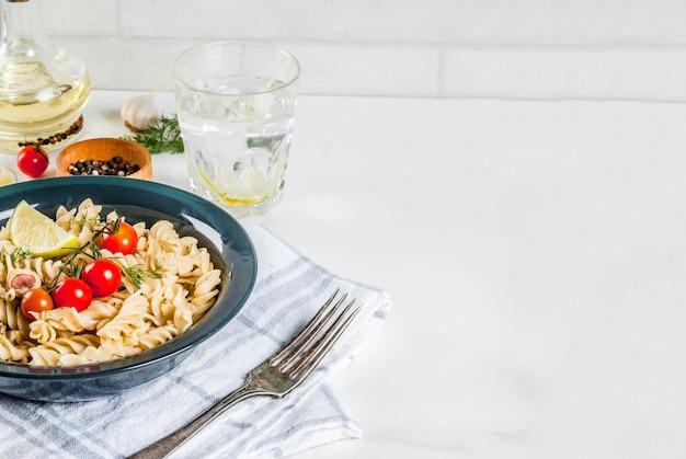 Fusilli de pasta italiana clásica con verduras y aceite de oliva.