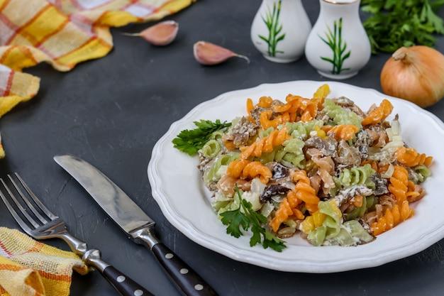 Fusilli pasta multicolor con verduras en un plato blanco sobre fondo oscuro