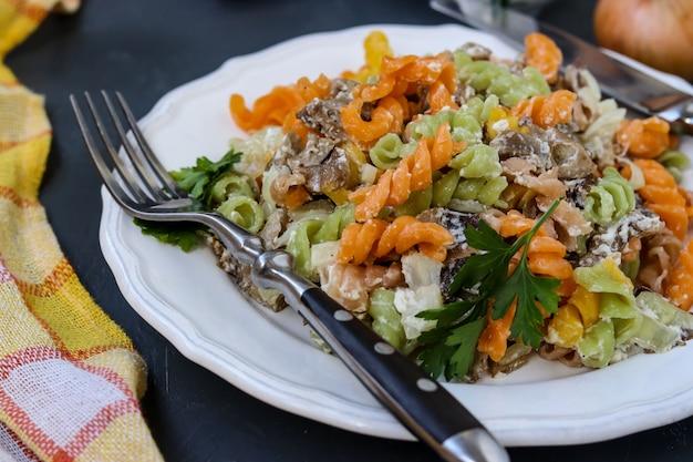 Fusilli pasta multicolor con verduras en un plato blanco sobre oscuro, enfoque selectivo