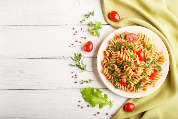 Fusilli pasta con salsa de tomate, tomates cherry, lechuga y hierbas