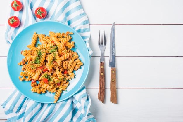 Fusilli de pasta con tomate y cubiertos en mesa de madera blanca