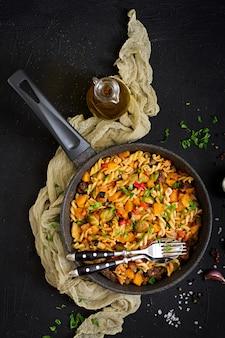 Fusilli pasta vegetal con calabaza, coles de bruselas, pimentón y trozos de hígado. vista desde arriba