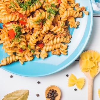 Fusilli vegetal vegetariano de las pastas en la placa azul sobre el fondo blanco
