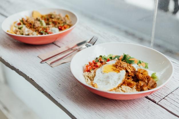 Fusión de alimentos aderezos para el tazón de arroz kimchi de cerdo, huevo frito orgánico, berenjena coreana y ensalada.