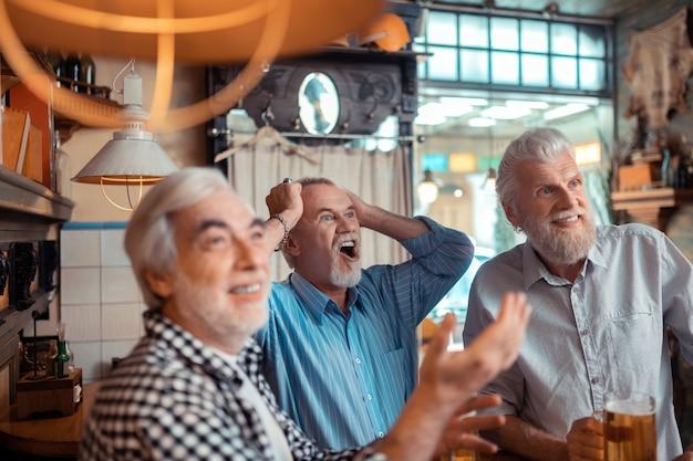 Fútbol con amigos. hombre jubilado de ojos azules que se siente emocional viendo fútbol con amigos