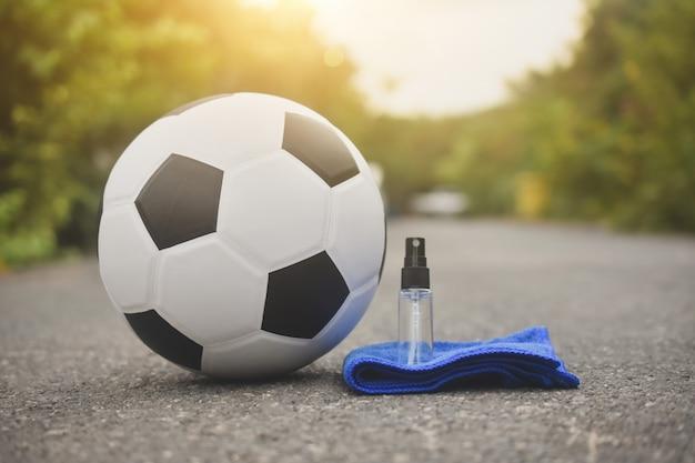 Fútbol fútbol y spray de alcohol para limpiar corona virus covid 19, new normal