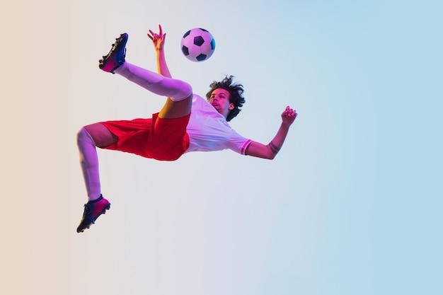 Fútbol o jugador de fútbol sobre fondo degradado en concepto de actividad de acción de movimiento de luz de neón