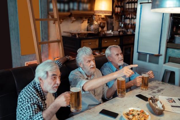Fútbol en pub. tres jubilados emocionales canas viendo fútbol en el pub