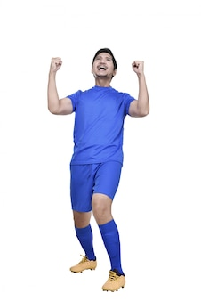 El futbolista masculino asiático emocionado que presenta celebra