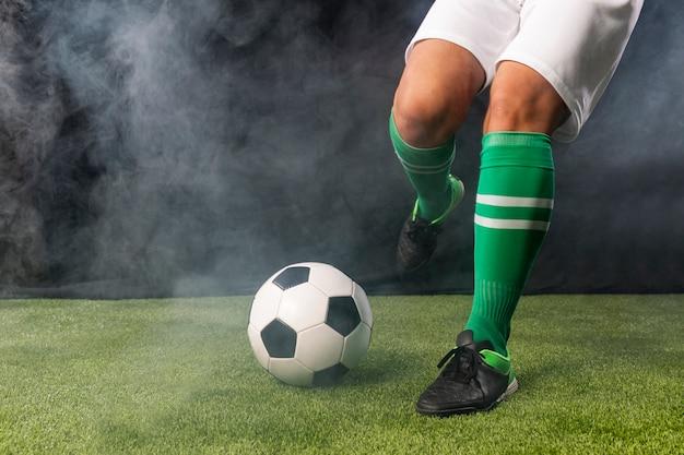 Futbolista en ropa deportiva pateando pelota