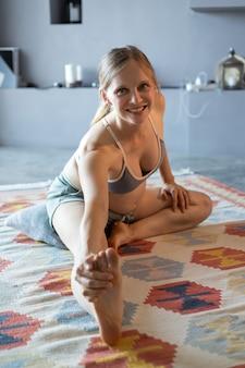 Futura madre alegre practicando yoga en casa