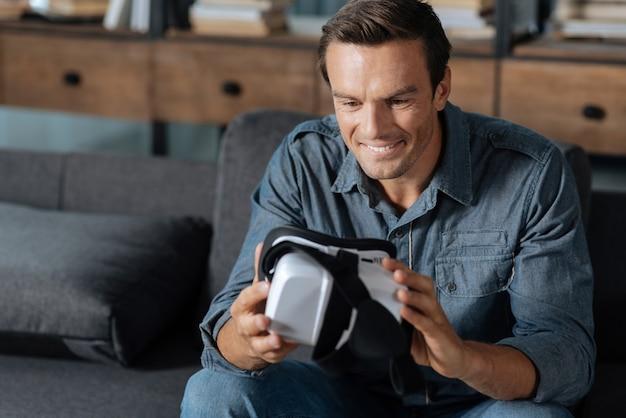 Futuro de los videojuegos. hombre guapo emocional fascinado sentado en su sala de estar