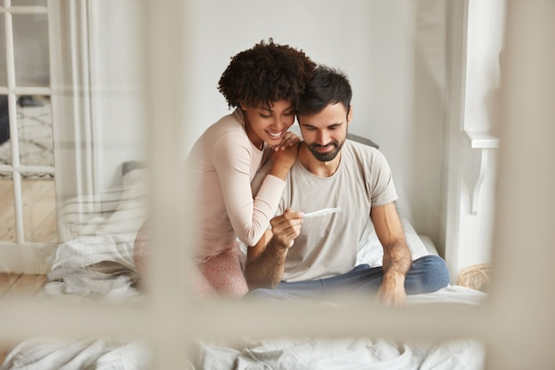 Los futuros padres felices de raza mixta miran con alegría la prueba de embarazo, se regocijan con las noticias positivas sobre el embarazo, se sientan juntos en la cama contra el interior doméstico.