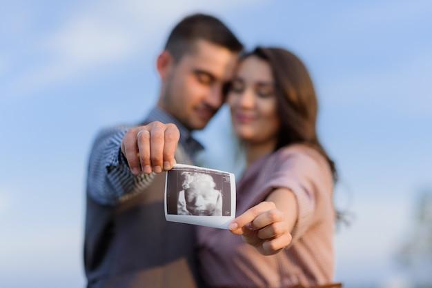 Los futuros padres sostienen una imagen monocroma de su futuro hijo al aire libre
