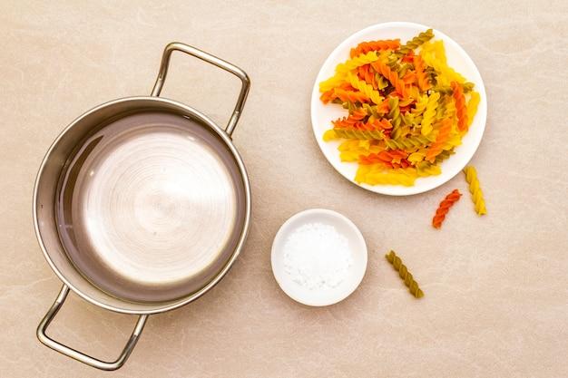 Fuzilli crudo con agua en una olla y sal. pasta multicolor en plato blanco sobre superficie de piedra. preparación para niños, vista superior, de cerca.