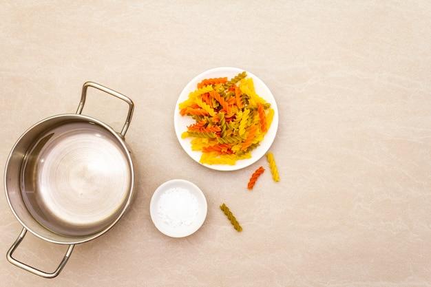 Fuzilli crudo con agua en una olla y sal. pasta multicolor en plato blanco sobre superficie de piedra. preparación para niños, vista superior, espacio de copia.