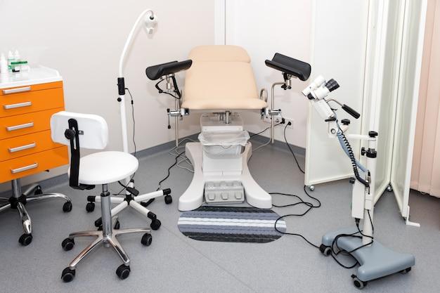 Gabinete ginecológico con silla y otros equipos médicos en clínica moderna.