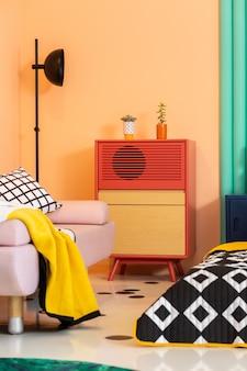 Gabinete rojo-naranja con dos suculentas en la sala de estar de diseño moderno y colorido.