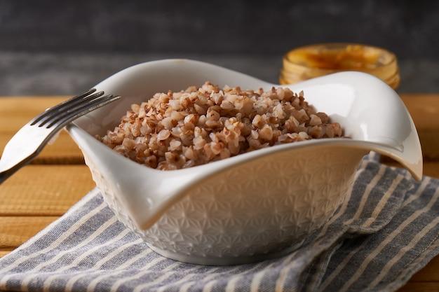Gachas de alforfón hervidas con mantequilla servidas en un plato low key fondo oscuro