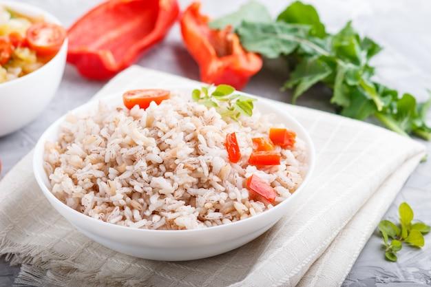 Gachas de arroz sin pulir con verduras guisadas y orégano en un tazón blanco sobre una superficie de hormigón gris. vista lateral, de cerca.