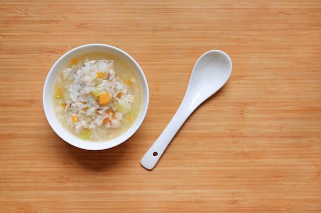 Gachas de avena para los alimentos para niños en el cuenco y la cuchara de cerámica blancos en el fondo de madera del tablero.