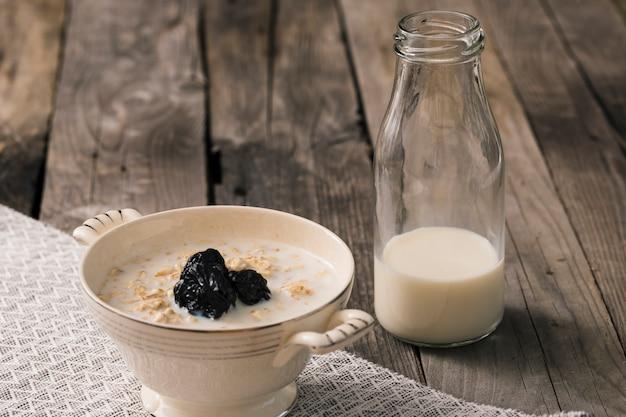 Gachas de avena con una botella de leche en la mesa rústica