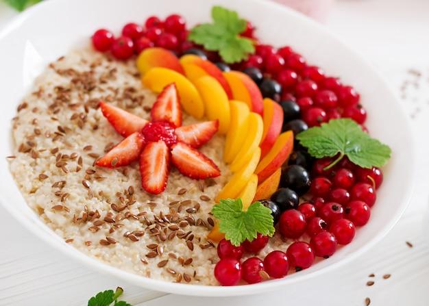 Gachas de avena sabrosas y saludables con bayas, semillas de lino y batidos. desayuno saludable. nutrición apropiada