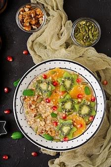Gachas de avena sabrosas y saludables con frutas, bayas y nueces. desayuno saludable. comida de fitness. nutrición apropiada. endecha plana. vista superior