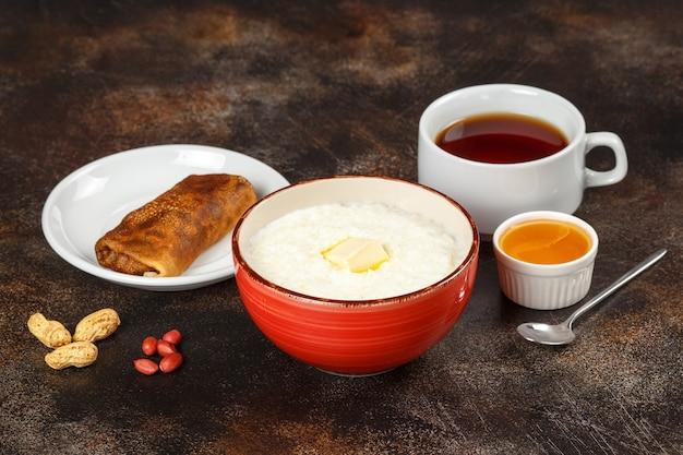 Gachas de avena en un tazón, crepes rellenos y té