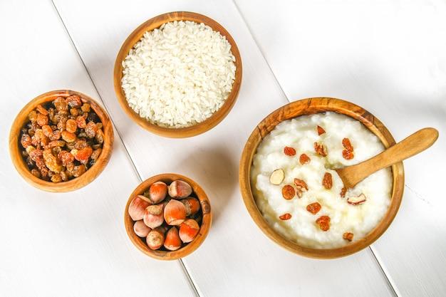 Gachas de leche de arroz con nueces y pasas en cuencos de madera sobre una mesa de madera blanca